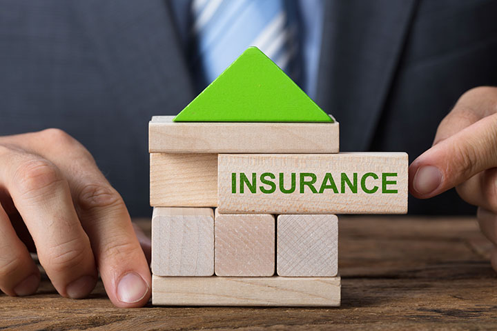 Closeup of businessman building house with insurance block on table